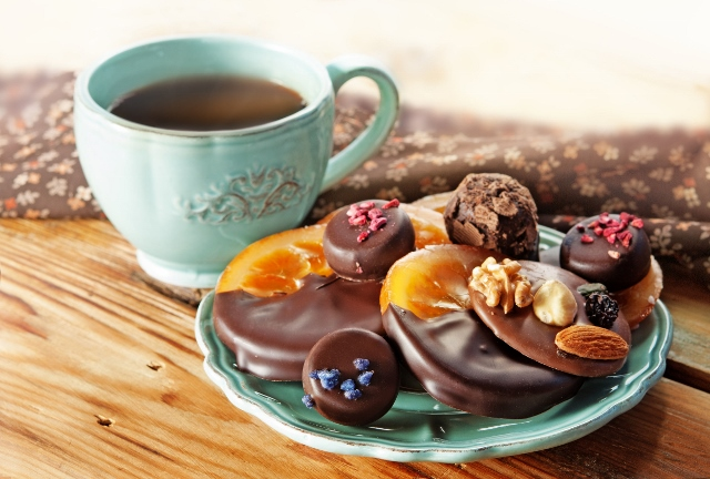 28466307 - cup of coffee, assortment of fine chocolates dark, and milk chocolate, orange in chocolate and truffle